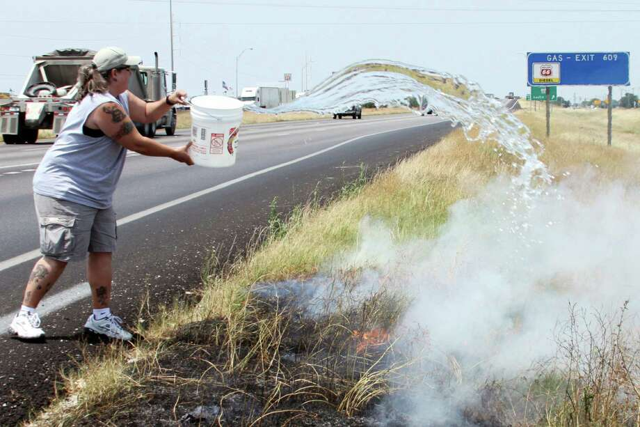 Carla Stewart-Norris and the staff of Los Cucos Mexican Cafe doused a grass fire that threatened to send thick smoke across Interstate 10 in Seguin. Photo: FORREST M MIMS 111