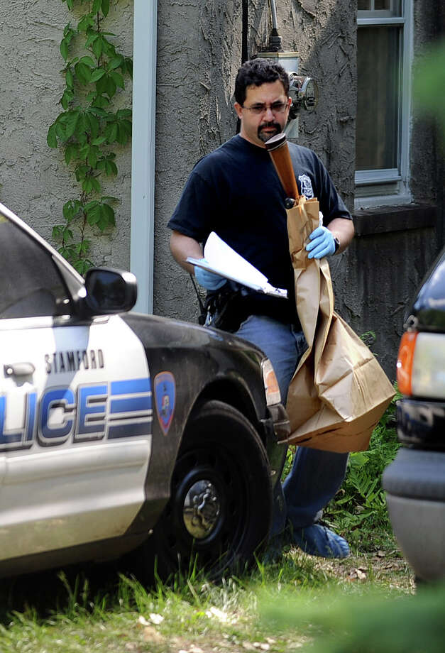 Stamford Police Officer Cory Caserta carries a shotgun out of the house at 1214 Long Ridge Road on Friday after it was used in a murder-suicide inside the house. Florence Beran and her daughter Susan lived at the home. Photo: Lindsay Niegelberg / Stamford Advocate