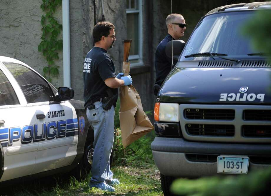 Stamford Police Officer Cory Caserta carries a shotgun out of the house at 1214 Long Ridge Road on Friday after it was used in a murder-suicide inside the house. Florence Beran and her daughter, Susan, lived at the home. Photo: Lindsay Niegelberg / Stamford Advocate