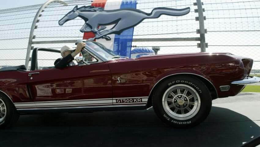 LEBANON, UNITED STATES: Carroll Shelby arrives in a 1968 GT500 KR during the celebration of the 40th Anniversary of the Ford Mustang 15 April, 2004 at the Nashville Super Speedway in Lebanon, TN. Shelby was the greatest single influence on America's racing posture in the post-1945 period with help in the engine design and racing operations of the Mustang. AFP PHOTO/Jeff HAYNES (Photo credit should read JEFF HAYNES/AFP/Getty Images) (AFP/Getty Images)