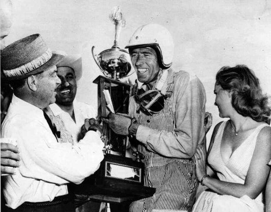 FILE - In this April 3, 1960 file photo, race car driver Carroll Shelby, center, of Dallas, receives his winner's trophy from promotion manager Dave Brandman, after winning the 200-mile International Grand Prix at the Riverside Raceways, in California. At right is Jan Harrison, the queen of the race. Shelby, the legendary race driver and Shelby Cobra sports car designer, has died at age 89. Shelby's company Carroll Shelby International says Shelby died Thursday, May 10, 2012, at a Dallas hospital. He had received a heart transplant in 1990 and a kidney transplant in 1996. (AP Photo, File) (AP)