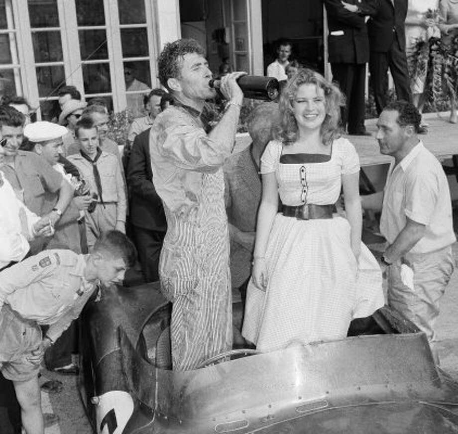 FILE - In this June 21, 1959 file photo, Texas driver Carroll Shelby enjoys a swig of champagne after combining with British veteran Roy Salvadori to win the 24-Hour Endurance Auto Classic at Le Mans, France. Dressing up the picture is Miss Sophie Destrade, of France, Miss Europe of 1959. Shelby, the legendary race driver and Shelby Cobra sports car designer, has died at age 89. Shelby's company Carroll Shelby International says Shelby died Thursday, May 10, 2012, at a Dallas hospital. He had received a heart transplant in 1990 and a kidney transplant in 1996. (AP Photo/Jacques Marqueton, File) (AP)