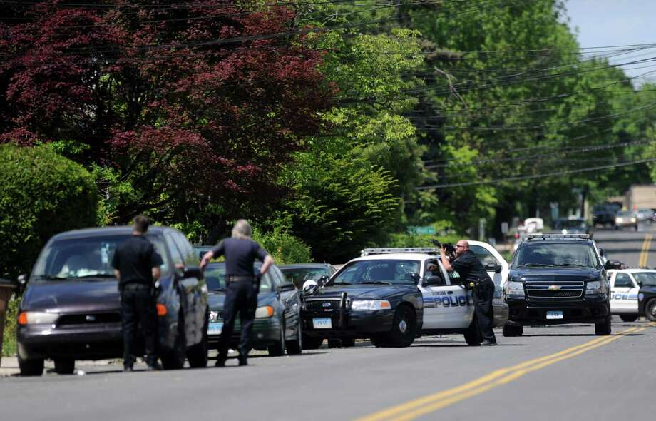 Stamford police officers surround a house at 293 Fairfield Avenue where a man with a gun was suspected to be inside on Friday, May 11, 2012. Photo: Lindsay Niegelberg / Stamford Advocate