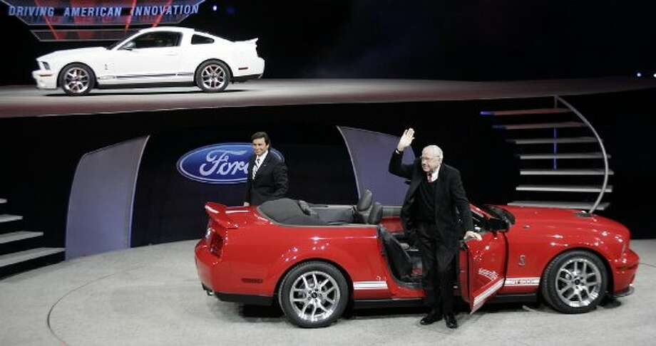 Detroit, UNITED STATES:  Carroll Shelby (R) waves from the door of the 2007 Ford Shelby GT500 as Ford Executive VP Mark Fields looks on 08 January 2006 during the press days at the N shownorth American International Auto Show at Cobo Hall in Detroit, Michigan. The auto show opens to the public 14 January.  AFP PHOTO/Jeff HAYNES  (Photo credit should read JEFF HAYNES/AFP/Getty Images) (AFP/Getty Images)