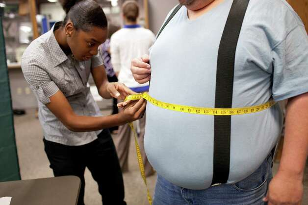 "Shaquilah Davis measures Mark Mertin in the HBO documentary, ""The Weight of the Nation."" More than two-thirds of adults are overweight or obese. Photo: HBO"