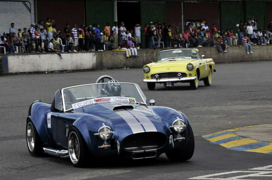 Colombian driver Michael Santins, drives his AC Shelby Cobra, of 1965, during a race of classic and vintage cars on the track of Cavasa, in Candelaria, Valle del Cauca department, Colombia, on November 7, 2010. It is first time that 52 cars manufactured before 1975 participate in a race.  AFP PHOTO/Luis ROBAYO Photo: LUIS ROBAYO, Getty Images / 2010 AFP