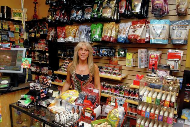 Tracey Scalzi stands behind the counter at her store Tracey's Smoke Shop and Tobacco LLC in Norwalk, Conn. on Friday May 11, 2012.  The state is trying to force her to pay cigarette taxes on roll-your-own smokes, either in court or through legislation. Photo: Dru Nadler / Stamford Advocate Freelance