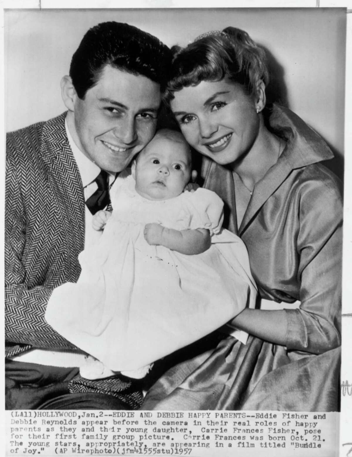 """AP CAPTION: HOLLYWOOD, JAN. 2, 1957 -- EDDIE AND DEBBIE HAPPY PARENTS-- Eddie Fisher and Debbie Reynolds appear before the camera in their real roles of happy parents as they and their young daughter, Carrie Frances Fisher, pose for their first family group picture. Carrie Frances was born Oct. 21. The young stars, appropriately, are appearing in a film titled """"Bundle of Joy."""" (AP WIREPHOTO). HOUCHRON CAPTION (11/16/1999): According to Eddie Fisher's new autobiography, things were not as happy as this photo indicates even before he left wife Debbie Reynolds, right, for Elizabeth Taylor. Fisher and Reynolds are pictured in 1957 with daughter Carrie Fisher."""