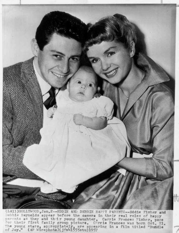 "AP CAPTION: HOLLYWOOD, JAN. 2, 1957 -- EDDIE AND DEBBIE HAPPY PARENTS-- Eddie Fisher and Debbie Reynolds appear before the camera in their real roles of happy parents as they and their young daughter, Carrie Frances Fisher, pose for their first family group picture.  Carrie Frances was born Oct. 21.  The young stars, appropriately, are appearing in a film titled ""Bundle of Joy.""  (AP WIREPHOTO).    HOUCHRON CAPTION (11/16/1999):  According to Eddie Fisher's new autobiography, things were not as happy as this photo indicates even before he left wife Debbie Reynolds, right, for Elizabeth Taylor.  Fisher and Reynolds are pictured in 1957 with daughter Carrie Fisher. / AP Wirephoto"