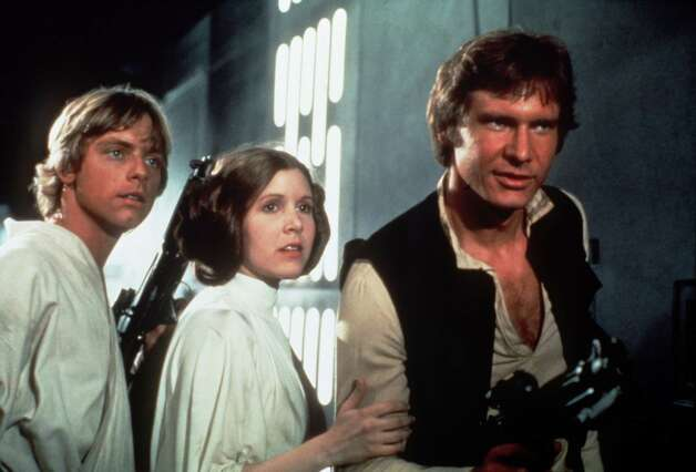 "Mark Hamill, left, Carrie Fisher, center, and Harrison Ford, right, are shown in a scene from the 1977 film ""Star Wars."" / handout slide"