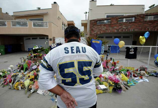 "San Diego Chargers fan Jerry Lopez looks over a memorial set-up in the driveway of the house of former NFL star Junior Seau Thursday, May 3, 2012, in Oceanside, Calif. Seau's apparent suicide stunned an entire city and saddened former teammates who recalled the former NFL star's ferocious tackles and habit of calling everybody around him ""Buddy.""  (AP Photo/Denis Poroy) Photo: Denis Poroy / FR59680 AP"