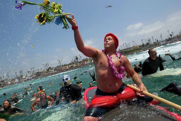 Wally Sani, a friend of Junior Seau, throws some flowers into the ocean off Oceanside, Calif., Sunday, May 6, 2012. A paddle-out was held to honor Seau, who committed suicide in his home Wednesday. Surfers said prayers and gave testimonials about the former football player. (AP Photo/UT San Diego, Sean M. Haffey) MANDATORY CREDIT MAGS OUT  NO SALES  TV OUT  SAN DIEGO COUNTY OUT  ARCHIVE OUT  FOREIGNS OUT  COMMERCIAL ONLINE USE OUT Photo: Sean M. Haffey / UT San Diego