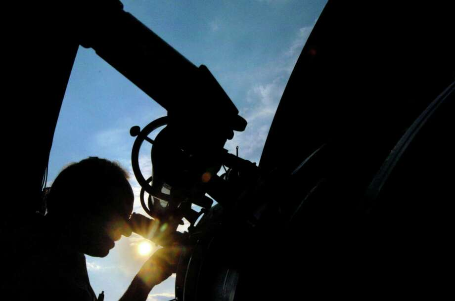Looking through the telescope at Westport's Rolnick Observatory Robert Meadows, of the Westport Astronomical Society, views the silhouette of Venus as the planet crosses the path of the sun in 2004. Astronomers say the transit of Venus will happen again in a few weeks on June 5 but won't happen again for over a hundred years.  Andrew Sullivan/File photo Photo: Andrew Sullivan/File Photo, ST