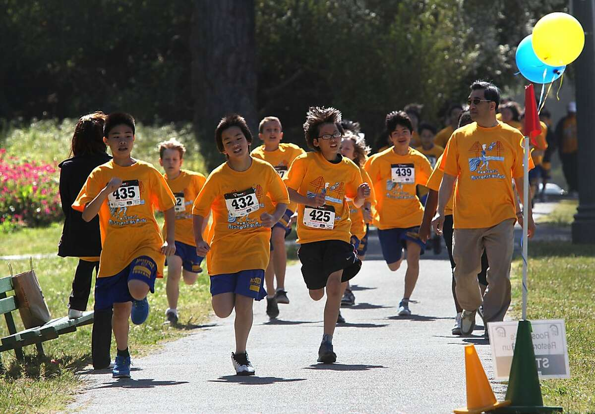 Children from Roosevelt Middle School including Simon Luu (front, left), Angus Li (front, middle) and Dion Chung (front, right) doing a 5k run in Golden Gate Park in San Francisco, Calif., on Friday, May 11, 2012.