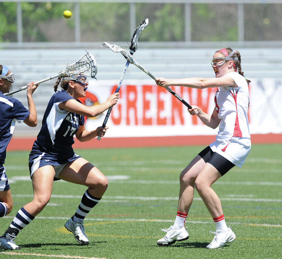 Claire Feeney, right, of Greenwich, scores a first half goal during the girls high school lacrosse match between Wilton High School and Greenwich High School at Greenwich, May 12, 2012. Wilton won the match 18-9. Covering on the play for Wilton is Liz Reda # 17. Photo: Bob Luckey / Greenwich Time