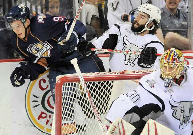 San Antonio Rampage's Scott Timmins, right, puts Oklahoma City Barons' Tyler Pitlick into the glass during the second period of an AHL hockey game, Friday, May 11, 2012, in San Antonio. Photo: Darren Abate, Darren Abate/pressphotointl.com / Darren Abate/pressphotointl.com