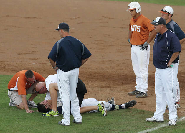 O'Connor pitcher Mark Ecker lays on the ground and is looked at by trainers after a hard collision with Madison runner John Stevens (third from right) near first base in the second inning of game 1 of a best of three series of the second round of Class 5A playoffs at NEISD on Friday, May 11, 2012. Ecker was helped off the field and never returned in the game. Stevens was ejected. Madison defeated O'Connor, 7-2. Kin Man Hui/Express-News. Photo: KIN MAN HUI, Kin Man Hui/Express-News / ©2012 San Antonio Express-News