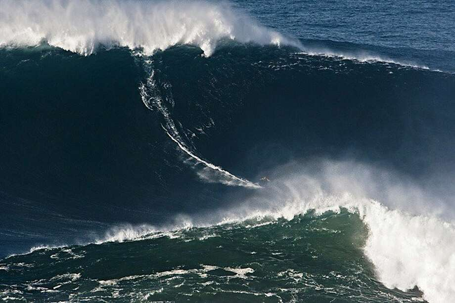 FILE - In this photo taken Nov. 1, 2011, and released by Nazare Qualifica/Polvo Concept Thursday, Nov. 10, 2011, Garrett McNamara, of Hawaii, surfs what is being called the tallest wave ever ridden at the Praia do Norte beach in Nazare, Portugal. McNamara took away honors at the Billabong XXL Big Wave Awards Friday May 4, 2012  and also set a world surfing record for surfing a wave measured by experts as 78 feet. A panel of big wave surfing and photography experts, who analyzed and measured the photos and videos of Garrett's ride, determined the height of the wave.  McNamara now has the Guinness World Record for the largest wave ever surfed after riding the 78-footer in November 2011 off the coast of Nazare, Portugal. (AP Photo/Nazare Qualifica/Polvo Concepts, Jorge Leal) EDITORIAL USE ONLY NO SALES Photo: Jorge Leal, Associated Press