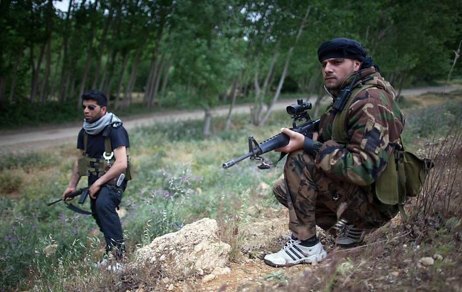 "Members of the Free Syrian Army ""commados brigade""  take position near the town of al-Qusayr in Syria's central Homs province, in anticipation of an attack by government regime forces on May 10, 2012. Opposition leader Burhan Ghalioun told reporters in Tokyo on May 11, that the Syrian regime is trying to destroy the UN-brokered peace plan aimed at ending 14 months of conflict. AFP PHOTO / STR-/AFP/GettyImages Photo: -, AFP/Getty Images"