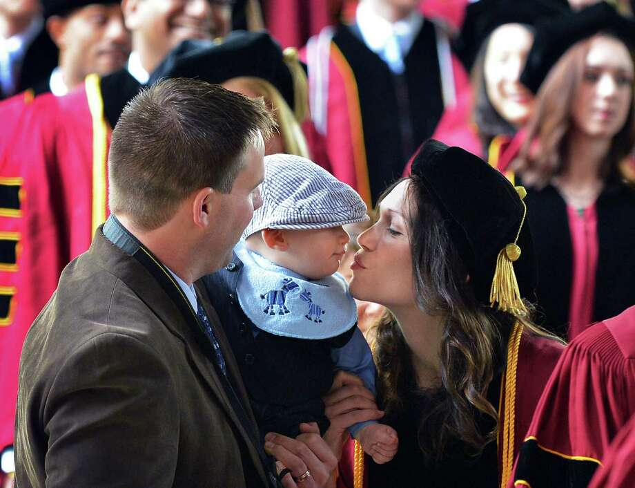 Justin French of Guilderland,left, holds up his baby son Julien French for mom, Albany Law School graduate Christine French, to kiss during the Processional of Albany Law's 161st Commencement at Saratoga Performing Arts Center  Friday May 11, 2012.  (John Carl D'Annibale / Times Union) Photo: John Carl D'Annibale / 00017188A