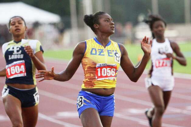 Ozen's Bealoved Brown, center, checks her winning time of 11.83 at the finish of the 4A girls 100 meter dash at the UIL Track & Field State Championships at Mike A. Myers Stadium, The University of Texas at Austin. May 11, 2012.  Valentino Mauricio/The Enterprise Photo: Valentino Mauricio