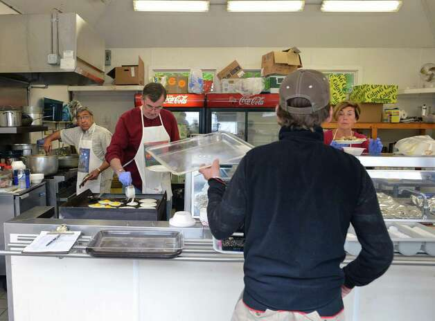 Backstretch workers file through the B.E.S.T (Backstretch Employee Service Team) breakfast kitchen at Saratoga Racecourse Thursday May 10, 2012.  In its third year, the program serves hundreds of meals throughout the spring and fall when there is no food available to the workers on the track.  (John Carl D'Annibale / Times Union) Photo: John Carl D'Annibale / 00017626A
