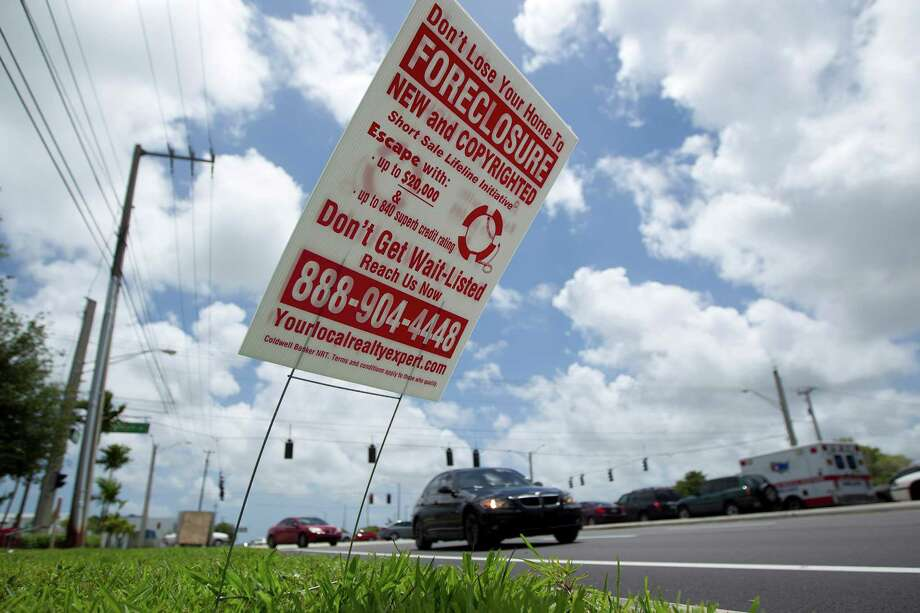 A sign offers help in foreclosure cases in Pembroke Pines, Fla. The eyesores have vexed the mayor of nearby Hollywood so much that he bought software that makes up to 20 robocalls a day to the numbers on the signs. Photo: J Pat Carter / AP