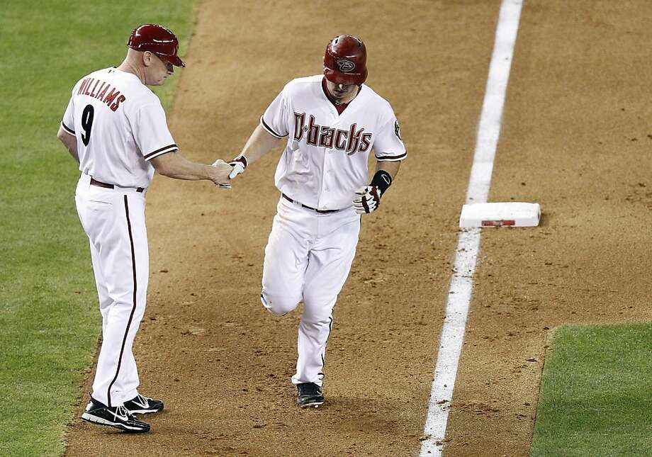 Arizona Diamondbacks' Paul Goldschmidt, right, is congratulated by third base coach Matt Williams, left, as he heads for home after hitting a two-run home run off San Francisco Giants pitcher Madison Bumgarner in the fifth inning of a baseball game, Friday, May 11, 2012, in Phoenix. (AP Photo/Paul Connors) Photo: Paul Connors, Associated Press