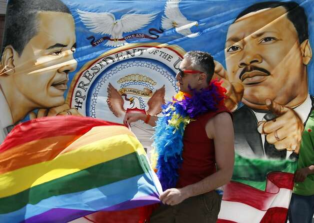 Trenton Garris waves his rainbow flag in front of a banner in support of President Barack Obama who was visiting the Paramount Theater one day after announcing his support for same sex marriage, in Seattle on Thursday, May 10, 2012. (AP Photo/Kevin P. Casey) Photo: Kevin Casey, Associated Press