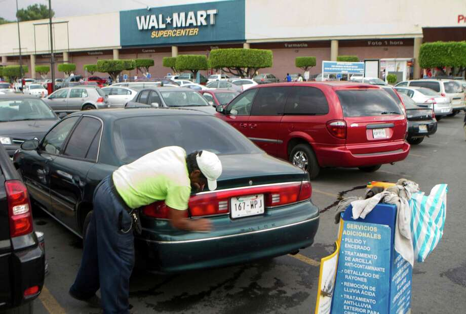 A car gets a cleaning outside a Walmart in Mexico City. The U.S. and Mexican governments reportedly are investigating the chain. / AP