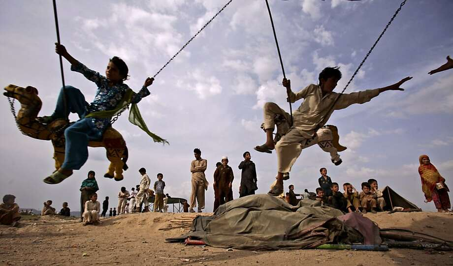 Pakistani children who fled their villages with their families due to fighting between security forces and militants in Pakistan's tribal area of Bajur, enjoy a ride on a merry-go-round at a makeshift entertainment park set up in a slum area on the outskirts of Islamabad, Pakistan, Friday, May 11, 2012. (AP Photo/Muhammed Muheisen) Photo: Muhammed Muheisen, Associated Press