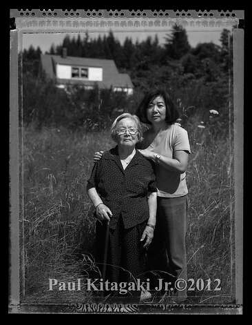 Fumiko Hayashida, 95, and her daughter Natalie Ong, 66, photographed July 20, 2006 on the family farm where they were evacuated from on Bainbridge Island, Waashington.  Fumiko Hayashida, a young mother of thirty-one, carries her 13 month-old daughter Natalie Kayo, holding her teddy bear, on March 30, 1942, walking at the Eagledale Ferry landing surrounded by armed soldiers to a waiting ferry on Bainbridge Island that would send her to Manzanar Internment Camp in California arriving by train on April 1, 1942 (April Fools Day). Photo: Paul Kitagaki Jr., Paul Kitagaki Jr. ©2012