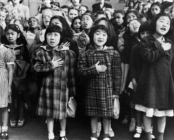 Second generation Japanese Americans Helene Nakamoto Mihara, 7, left, and Mary Ann Yahiro, 7, center, recite the Pledge of Allegiance the Raphael Weill School in San Francisco, California before being sent to the Topaz Internment Camp in Utah in April, 1942. Photograph by Dorothea Lange Photo: Dorothea Lange