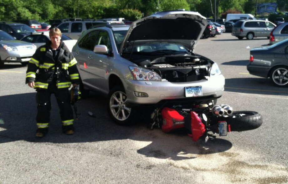 A firefighter inspects the scene of a Saturday morning collision between a motorycle and SUV in the parking lot of the Edge Fitness Center on Kings Highway Cutoff. Photo: Fairfield Fire Department / Fairfield Citizen contributed