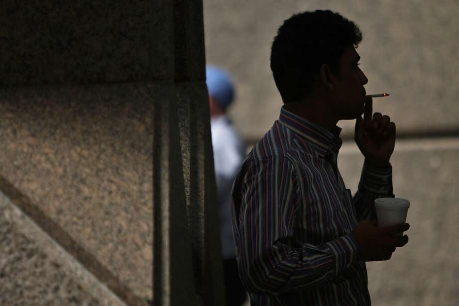 NEW YORK - MARCH 30:  A man smokes a cigarette March 30, 2009 in New York City. On April 1 a new federal excise tax on tobacco will officially commence, driving the per-pack tax from 39 cents to $1.01.The tax will affect all tobacco products, including cigars and pipes, and the money earned will be used to expand health coverage for low-income children.  (Photo by Spencer Platt/Getty Images) Photo: Spencer Platt, Getty Images