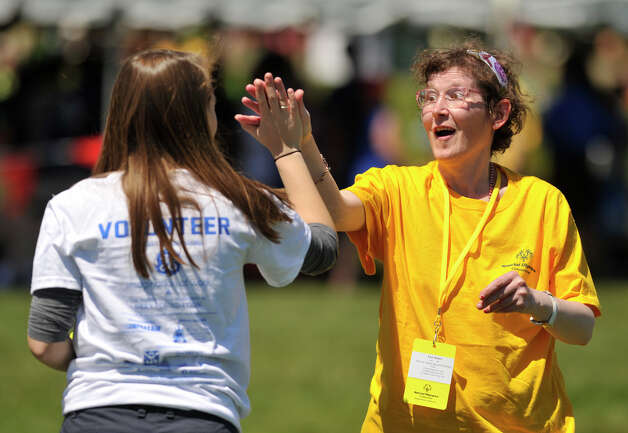 National Charity League volunteer Alicia DeLalla, left, of Ridgefield, high-fives Lore Knorr, of Brookfield, representing Ability Beyond Disability, after Knorr's softball throw during the Special Olympics Connecticut Northwest Regional Games at Danbury High School on Saturday, May 12, 2012. Photo: Jason Rearick / The News-Times