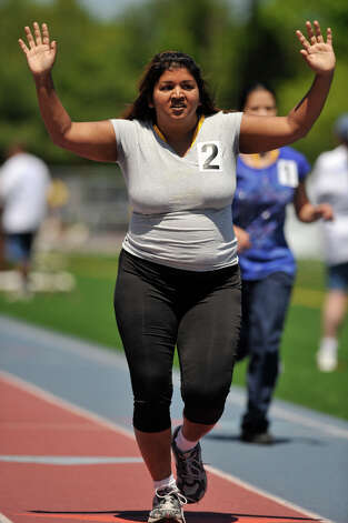 Priya Karabin, of Southington, crosses the finish line, completing the 400-meter run during the Special Olympics Connecticut Northwest Regional Games at Danbury High School on Saturday, May 12, 2012. Photo: Jason Rearick / The News-Times