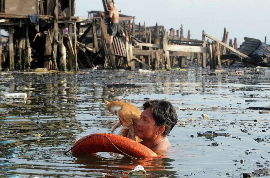 A resident holds his cat at the site of a fire in a shanty town in Manila on May 12, 2012. Shanty homes were destroyed by a huge fire that swept through Manila's largest coastal slum on May 11. Photo: JAY DIRECTO, AFP/Getty Images / AFP