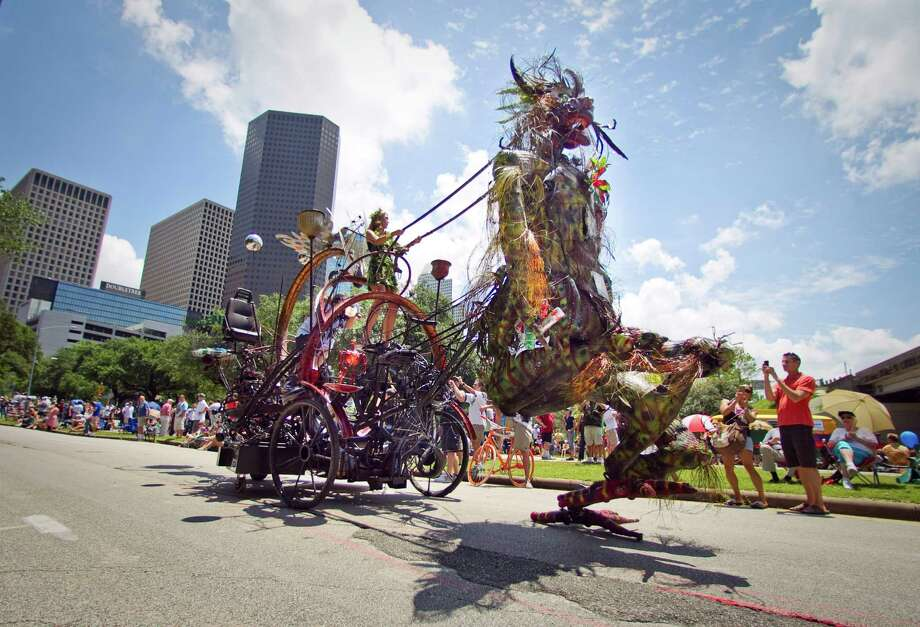 The art car 'Mr Green is a walking machine,' made by Houston artist Mark 'Scrapdaddy' Bradford, walks in the 25th Anniversary Art Car Parade, Saturday, May 12, 2012, in Houston. The car is made almost entirely with recycled materials. Photo: Nick De La Torre, Houston Chronicle / © 2012  Houston Chronicle