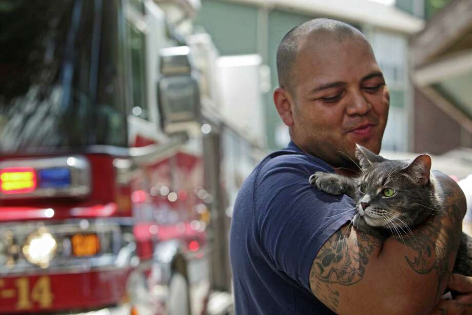 """""""As long as I've got my cat, that's all that matters,"""" Pete Terrazas said as he holds his cat, Bubbles, after a fire in the apartment below his forced them outside at the Summit of Thousand Oaks apartment complex in San Antonio on Saturday, May 12, 2012. Terrazas was forced to leave his apartment when he couldn't find Bubbles or his other cat, Cloe, but was allowed to re-enter once the fire was out to find them in their hiding places and take them outside. Photo: Lisa Krantz, SAN ANTONIO EXPRESS-NEWS / SAN ANTONIO EXPRESS-NEWS"""