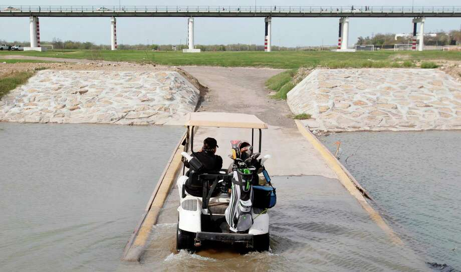 Roberto Gonzalez, of Eagle Pass, drives on through a canal, which converges into the Rio Grade, toward the International Bridge as continues his golf game at the Eagle Pass Golf Course on Tuesday, on March 6, 2012, in Eagle Pass.  Large groups of illegal immigrants use to cross the golf course, and it was no longer safe for golfers to use facility. Apprehensions have dropped in the Del Rio Sector, with the enforcement of Operation Streamline and a 'Zero Tolerance' policy. Photo: Mayra Beltran, Houston Chronicle / © 2012 Houston Chronicle