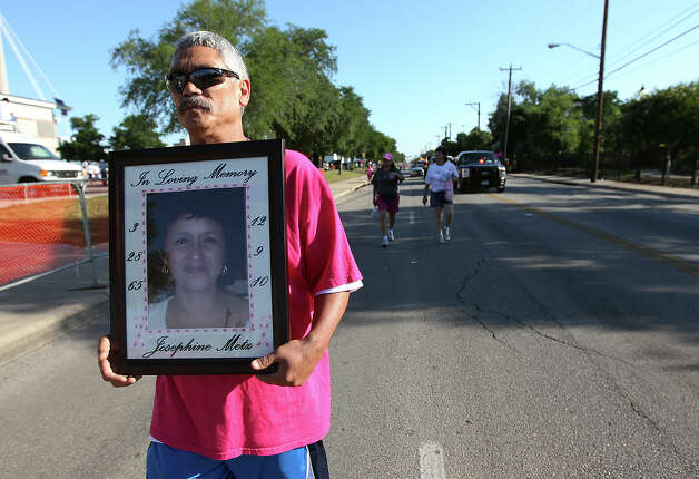 John Metz carries a portrait of his wife, Josephine, who passed away due to cancer in 2010 as he brings up the back of the group of participants at the 2012 Susan G. Komen San Antonio Race for the Cure on Saturday, May 12, 2012. Kin Man Hui/Express-News. Photo: Kin Man Hui, Kin Man Hui/Express-News / San Antonio Express-News