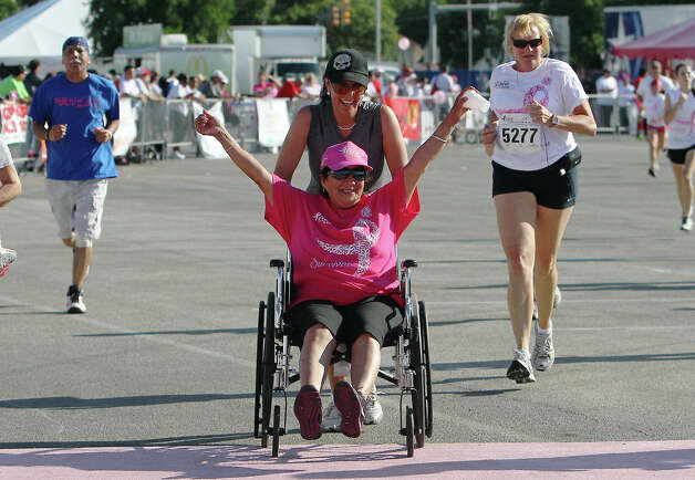 Mary Jane Reyna, seated in a wheelchair, celebrates crossing the finish line while being assisted by her sister, Patricia Martinez, at the 2012 Susan G. Komen San Antonio Race for the Cure on Saturday, May 12, 2012. Reyna said she has been cancer-free for three years. Kin Man Hui/Express-News. Photo: Kin Man Hui, Kin Man Hui/Express-News / San Antonio Express-News