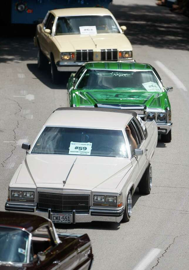 Lowriders from the Latin Fantasy car club jack their vehicles with their hydraulic systems during the 25th Anniversary Art Car Parade, Saturday, May 12, 2012, in Houston. Photo: Nick De La Torre, Houston Chronicle / © 2012  Houston Chronicle