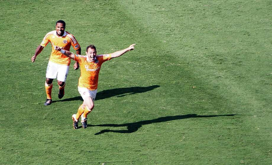 The Houston Dynamo's Brad Davis right celebrates after scoring a goal against the D.C. United during the second half as teammate Jermaine Taylor left, looks on in MLS game action at BBVA Compass Stadium Saturday, May 12, 2012, in Houston. Photo: James Nielsen, Chronicle / © Houston Chronicle 2012