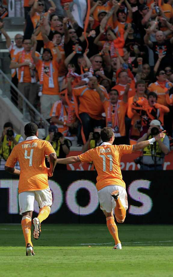 Houston Dynamo Jermaine Taylor (4) celebrates with Brad Davis (11) who scored a goal in the second half against D.C. United during the soccer game at BBVA Compass Stadium on Saturday, May 12, 2012, in Houston. Dynamo play first game in new BBVA Compass Stadium. Photo: Mayra Beltran, Houston Chronicle / Houston Chronicle