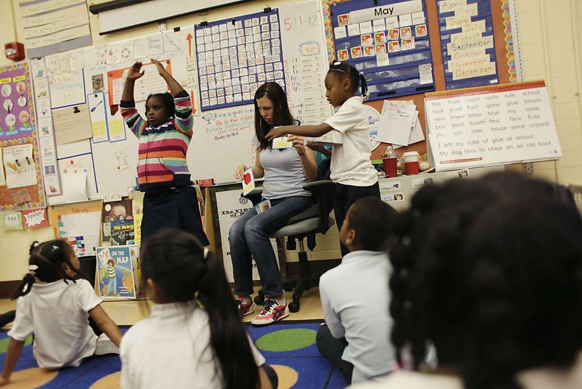 Nia Ross (center) gets help from Chantel Cade (left), 6, and Breana Collins (right), 7, as she goes through the alphabet with her first grade class at Dr. George Washington Carver Elementary School on Friday, May 11, 2012 in San Francisco, Calif.