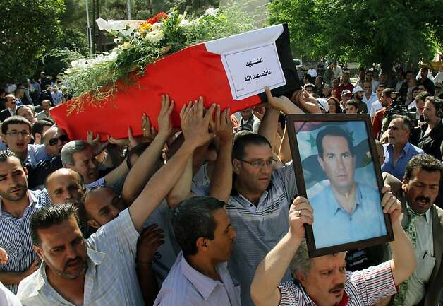 "A Syrian mourner leads the funeral carrying a picture of a slain man while others carry his coffin with Arabic that reads ""The Martyr, Atef Abdullah"" during a mass funeral procession for several Syrians killed in a twin suicide bombings, in Damascus, Syria Saturday May 12, 2012. A video posted online in the name of a shadowy militant group late Friday claimed responsibility for twin suicide bombings in the Syrian capital this week that killed 55 people. (AP Photo/Bassem Tellawi) Photo: Bassem Tellawi, Associated Press"