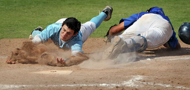 Jaguar baserunner Zach Hammer slips under the tag of catcher Adrian Gallegos to score the tying run in the sixth inning as  Johnson beats South San 5-4 in the final game of a three game series at South San High School on May 12, 2012.  Tom Reel/ San Antonio Express-News Photo: TOM REEL, Express-News / San Antonio Express-News