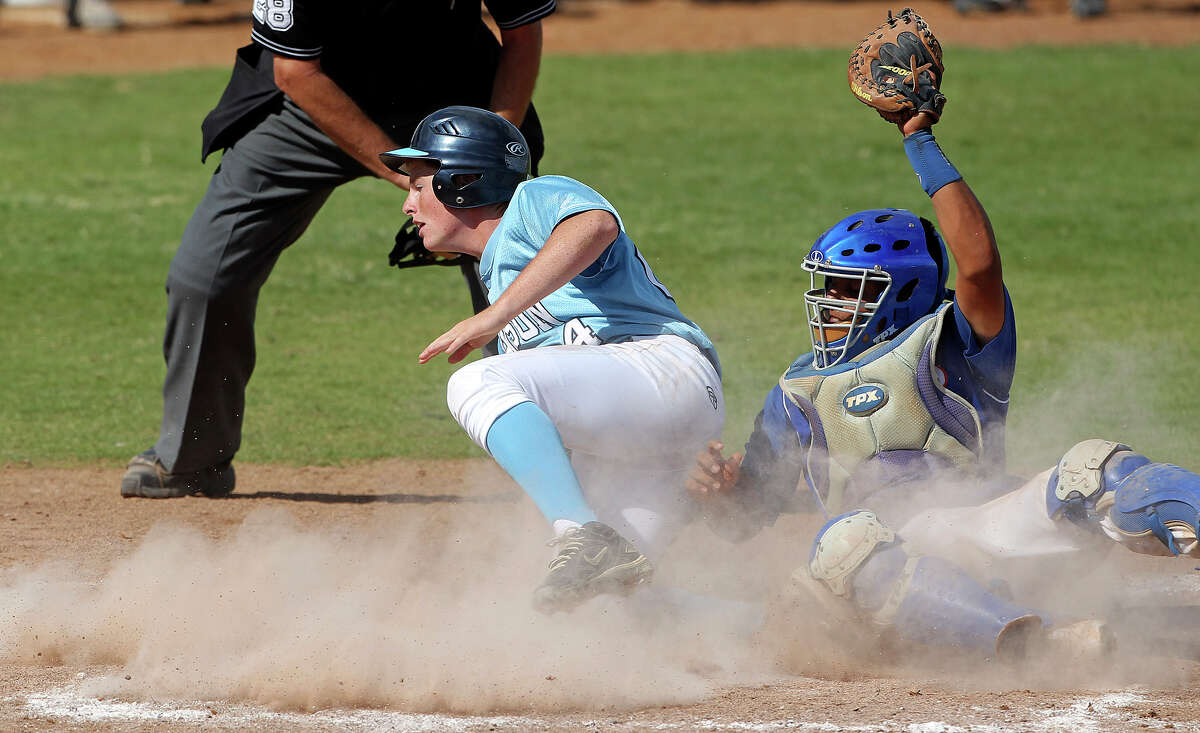 Bobcat catcher Adrian Gallegos hoist the ball high after getting the tag out on Reed Blanton at the plate as Johnson beats South San 5-4 in the final game of a three game series at South San High School on May 12, 2012. Tom Reel/ San Antonio Express-News